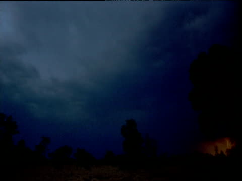 Clouds gather and lightning strikes as dusk falls in outback, Northern Territory, Australia