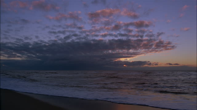 clouds glow above waves washing into shore. - insel sylt stock-videos und b-roll-filmmaterial