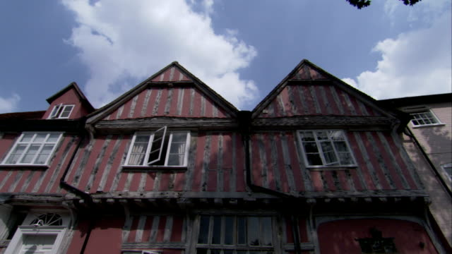 clouds hang above medieval houses in lavenham, england. available in hd. - lavenham stock-videos und b-roll-filmmaterial