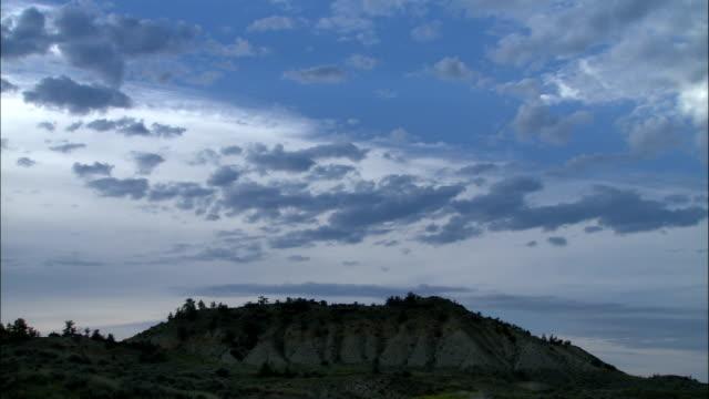 vidéos et rushes de clouds hang over a rocky landscape. - montana
