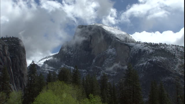 vídeos de stock, filmes e b-roll de clouds hover over the half dome mountain peak in yosemite national park. - condado de mariposa