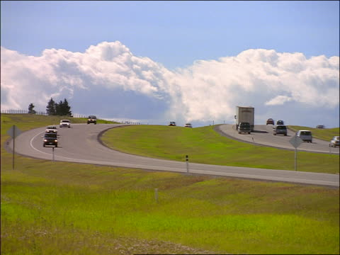 clouds in blue sky over traffic on country highway rounding curve toward camera / banff, alberta - alberta stock videos & royalty-free footage