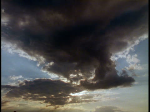 vidéos et rushes de t/l clouds - large grey cloud mass disperses overhead to camera, silver-edged clouds, blue sky - répandre