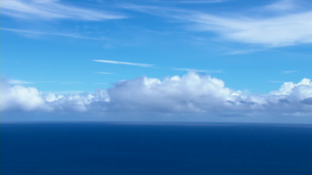 Clouds lie low on the horizon over the Pacific Ocean.