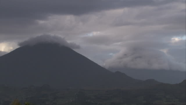 Clouds lie low over volcanoes. Available in HD.