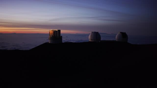 Molnen upplyst av sunset runt teleskopen på toppen av Mauna Kea, vulkanen på Hawaiis Big Island