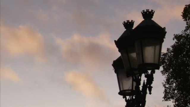 vídeos y material grabado en eventos de stock de clouds move across the sky behind an ornate streetlamp. available in hd. - ornate