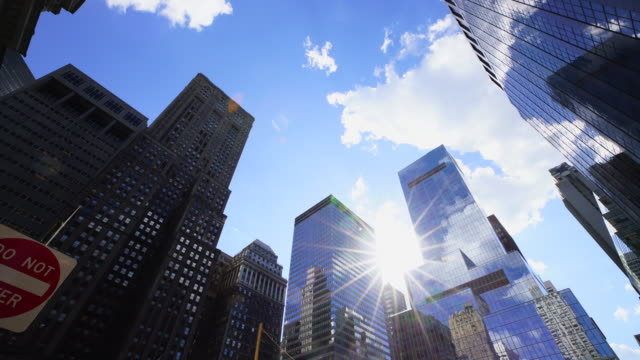 stockvideo's en b-roll-footage met clouds move over the skyscrapers and the sun shines from among the buildings at 42nd street midtown manhattan new york city. - low angle view