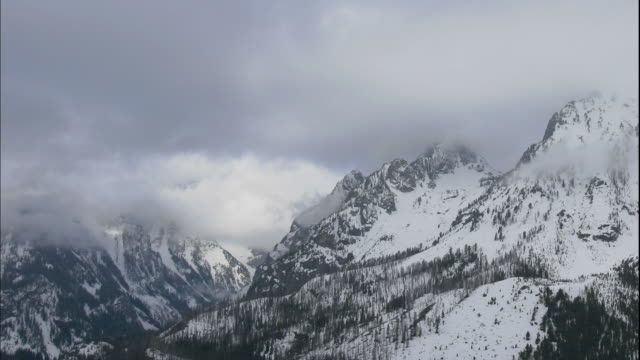 Clouds move over the snowy Grand Tetons in Grand Teton National Park.