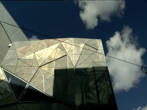 Clouds move slowly above irregular shaped exterior of Federation Square building Melbourne