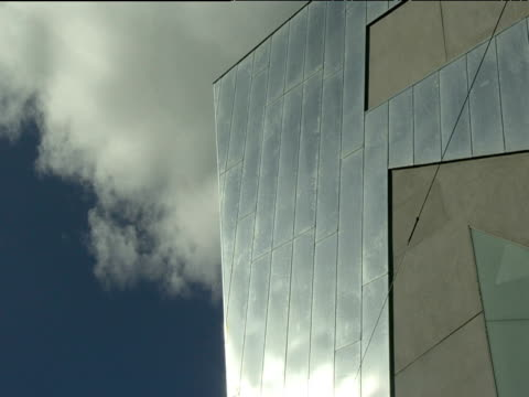 Clouds move slowly above shiny metal exterior of Federation Square building Melbourne