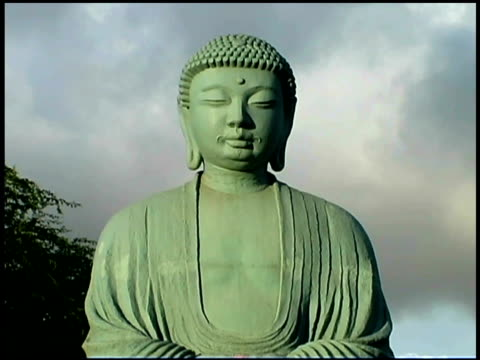 clouds move slowly behind a close-up of a buddha statue. - female likeness stock videos & royalty-free footage