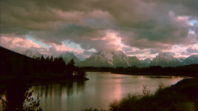 clouds move through the sky over  mt. moran and oxbow bend in grand teton national park. - mt moran stock videos & royalty-free footage