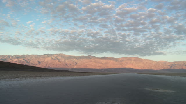 t/l ws clouds moving above badwater basin / death valley national park, california, usa - stationary process plate stock videos and b-roll footage
