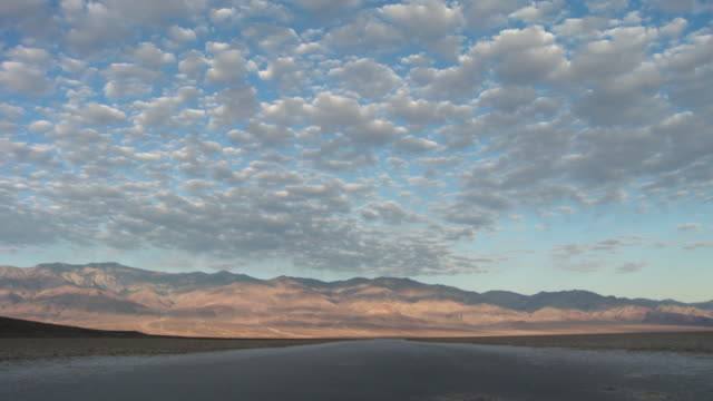 ws clouds moving above badwater basin / death valley national park, california, usa - stationary process plate stock videos and b-roll footage