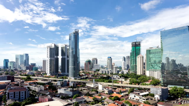 vídeos de stock e filmes b-roll de clouds moving above the jakarta skyline in the indonesia capital city - indonesia