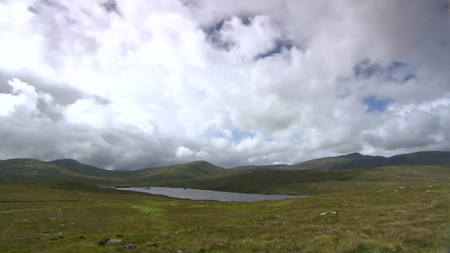 ws t/l clouds moving across derryveagh mountains near lake / glenveagh national park, donegal, ulster, ireland - アルスター州点の映像素材/bロール