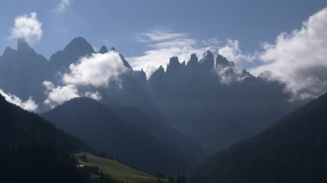 Clouds moving around the Geisler mountain group at Val di Funes. South Tyrol, Alto Adige, Val di Funes, Geissler Mountains, Dolomites, European Alps, Italy.