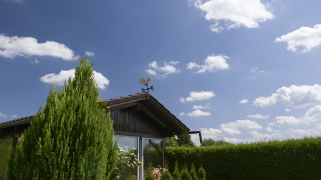 TL / Clouds moving on sky over pergola with weather vane