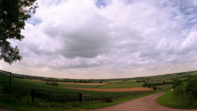 t/l, ws, pan, fish eye, clouds moving over farmland, cotswolds, oxfordshire, england - cotswolds stock videos & royalty-free footage