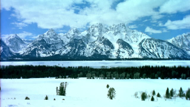 t/l ws clouds moving over grand tetons in winter / jackson, wyoming, usa - grand teton stock-videos und b-roll-filmmaterial