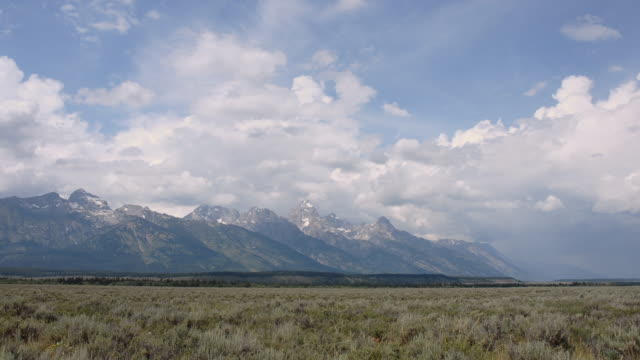 t/l ws clouds moving over grassy field with grand tetons in background/ grand teton national park, wyoming - grand teton stock-videos und b-roll-filmmaterial