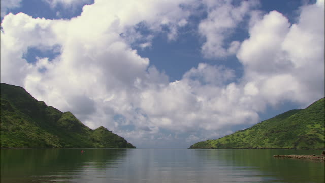 t/l ws clouds moving over green mountains and water on komodo island, boats traveling across bay / komodo national park, east nusa tenggara, indonesia - insel komodo stock-videos und b-roll-filmmaterial