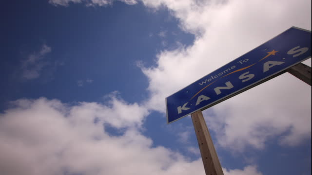 WS PAN T/L Clouds moving rapidly over 'Welcome to Kansas' sign / Kansas, USA