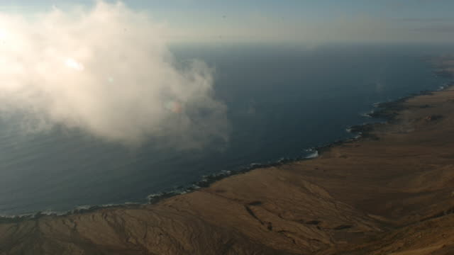 clouds obscure a desert coast. available in hd. - pacific ocean stock videos & royalty-free footage