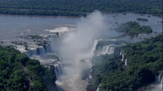 vídeos y material grabado en eventos de stock de clouds of mist float above the cascading terraces of iguazu falls in south america. available in hd. - cataratas del iguazú