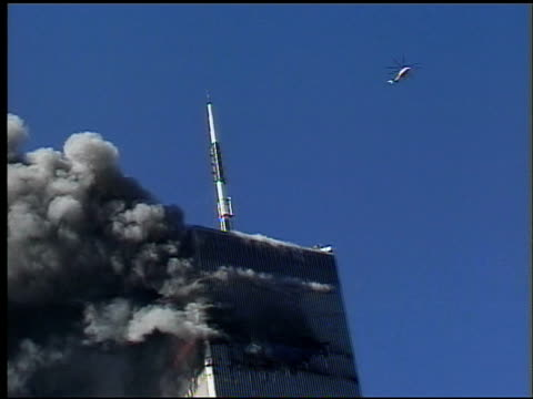 clouds of smoke around Tower 1 / Police helicopter flies close to roof of tower then flies away as Tower 2 collapses in mass of debris / chaos people...