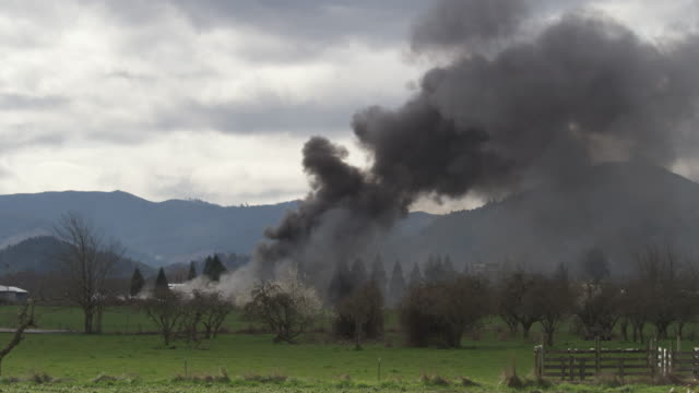 clouds of smoke from a distant fire across a field - distant stock videos and b-roll footage