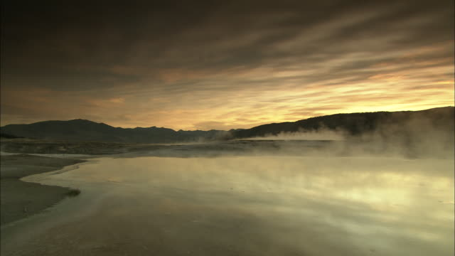 stockvideo's en b-roll-footage met clouds of steam rise from the yellowstone river under streaky golden clouds. - yellowstone national park