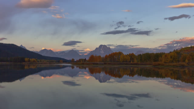 time lapse long wide shot clouds over grand teton with reflection in snake river at oxbow bend in foreground at sunrise, wyoming - grand teton stock-videos und b-roll-filmmaterial