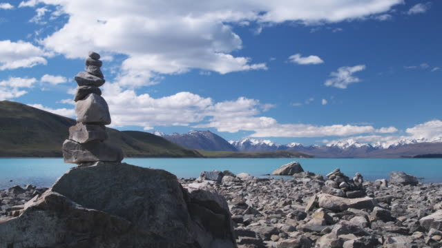 vídeos y material grabado en eventos de stock de t/l, ws, clouds over lake tekapo and mountains, stack of rocks in foreground, south island, new zealand - montón de piedras