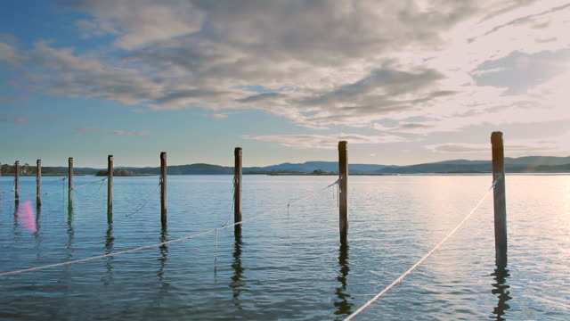 stockvideo's en b-roll-footage met ws t/l clouds over mooring posts standing like sentinels / mallacoota, victoria, australia - houten paal