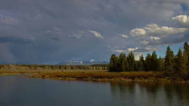 time lapse wide shot clouds over oxbow bend on snake river with tetons in background, grand teton national park, wyoming - スネーク川点の映像素材/bロール