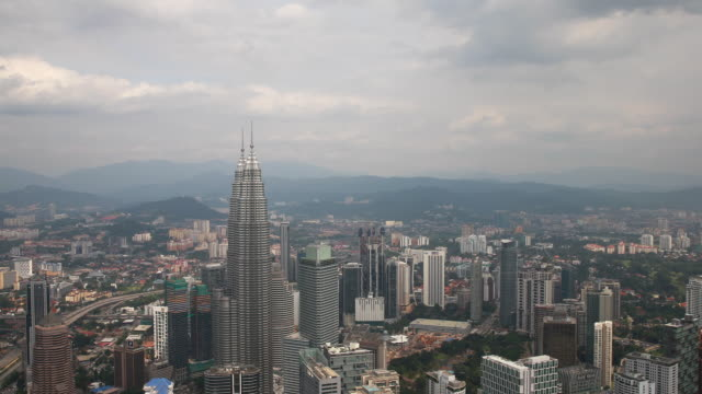 Clouds over Petronas Towers and Kuala Lumpur downtown seen from menara tower