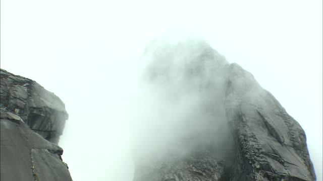 clouds over rock face of mount kinabalu in malaysia  - mt kinabalu stock videos and b-roll footage