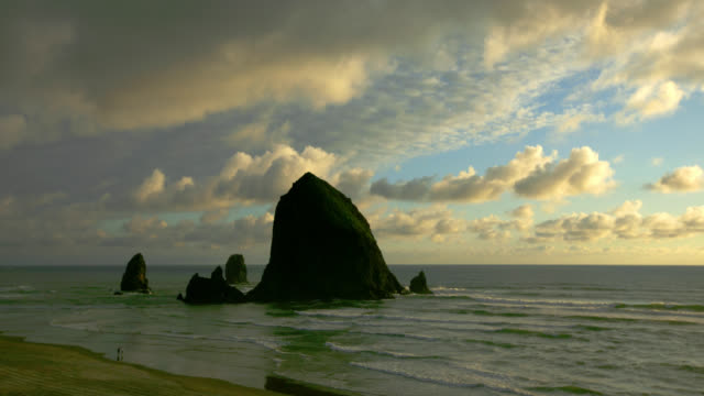 time lapse wide shot clouds over rock formation in ocean near beach with people from day to night, cannon beach, oregon - cannon beach stock videos & royalty-free footage