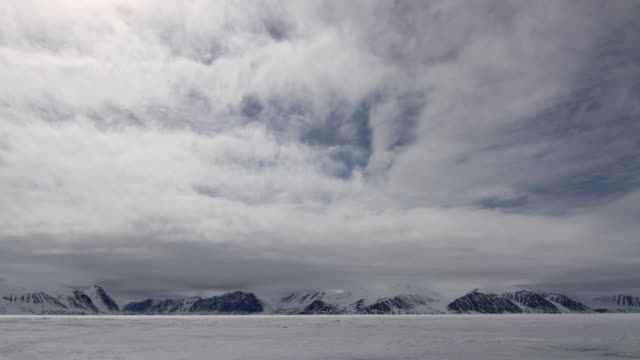 t/l ws clouds over snowy mountains / pond inlet, nunavut, canada - nu stock videos & royalty-free footage