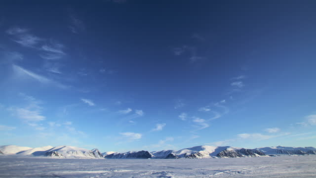 t/l ws clouds over snowy mountains / pond inlet, nunavut, canada - horizon stock-videos und b-roll-filmmaterial