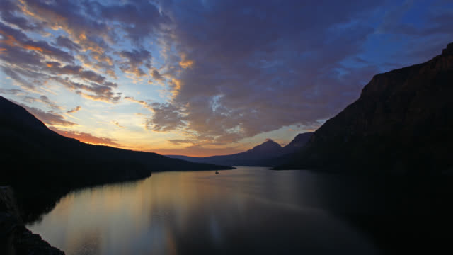 time lapse wide shot clouds over st mary lake and silhouetted mountains at sunrise in glacier national park, montana - us glacier national park stock videos & royalty-free footage