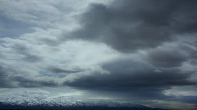 clouds over white mountain range, nevada - nube temporalesca video stock e b–roll