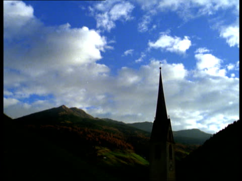 clouds pass over a church steeple in the mountains. - steeple stock videos & royalty-free footage