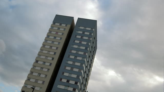 clouds pass over a high rise tower block in north london - 公営アパート点の映像素材/bロール