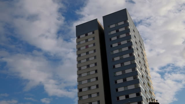 stockvideo's en b-roll-footage met clouds pass over a high rise tower block in north london - gevel