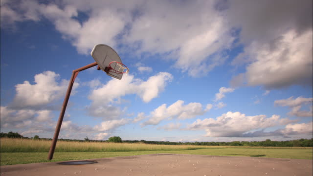 clouds pass over a rural basketball court. - basketball hoop stock videos & royalty-free footage