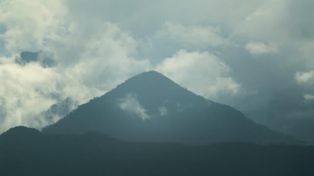 vídeos de stock e filmes b-roll de clouds pass over forested hills. - storm cloud