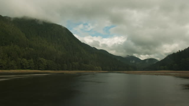 Clouds pass over forested inlet as river rises.